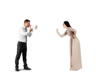 Woman showing her fist to screaming man. Emotional women showing her fist to screaming men with megaphone. isolated on white background Royalty Free Stock Photography