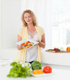 Woman showing her healthy food in her kitchen Royalty Free Stock Photo