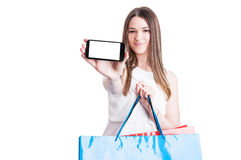 Woman showing her mobile phone while doing shopping Royalty Free Stock Image