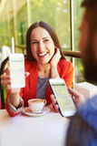 Woman showing her mobilephone. Laughing young women showing her mobilephone to men at cafe Stock Images