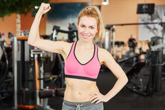 Woman showing her muscle and cletching her fist Stock Images