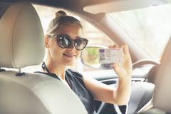 Woman showing her new driver license in a car royalty free stock photo