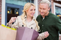 Woman showing her purchases to boyfriend at shopping mall Stock Photography