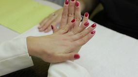Woman showing her red gel manicure in beauty salon