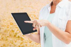 Woman showing her tablet in a field Stock Photography
