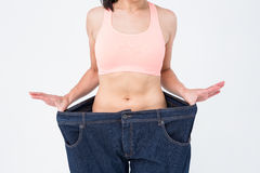 Woman showing her waist after losing weight. On white background Royalty Free Stock Photos