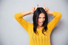 Woman showing horns with her fingers Stock Photo