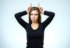 Woman showing horns with her fingers Royalty Free Stock Photography