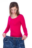Woman showing how much weight she lost. Healthy lifestyles conce. Pt isolated on white background Stock Photos