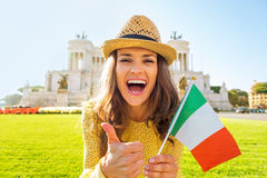 Woman showing italian flag and thumbs up in Rome. Portrait of happy young woman showing italian flag and thumbs up on piazza venezia in rome, italy royalty free stock photos