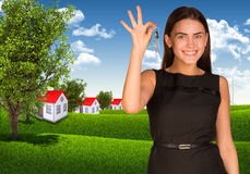 Woman showing key and houses with landscape Stock Image