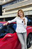 Woman showing key of new red sports car. Happy woman showing key of new red sports car Royalty Free Stock Photography