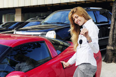 Woman showing key of new red sports car. Happy woman showing key of new red sports car Stock Photography