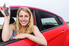Woman showing keys. Attractive blonde in a car showing keys Royalty Free Stock Images