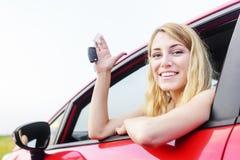 Woman showing keys. Beautiful woman in a car showing keys Royalty Free Stock Photo