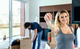 Woman showing keys while her husband unpacks. Young women showing the keys of her new house while her husband unpacks boxes. Selective focus on keys in Stock Photography