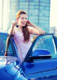Woman showing keys of new car. Portrait happy smiling young attractive woman buyer standing next to new blue car showing keys  outside dealer, dealership lot Stock Photos