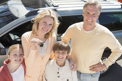 Woman Showing Keys While Standing With Family Against Car royalty free stock photos