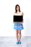 Woman showing laptop blank screen. Happy young woman showing laptop blank screen stock images