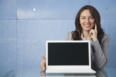 Woman showing laptop. Businesswoman showing a laptop screen stock photography