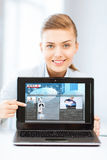 Woman showing laptop pc with news Stock Image