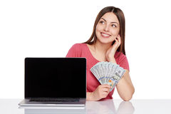 Woman showing laptop screen. Smiling woman showing laptop computer screen holding us dollar money in hand , looking out of frame, isolated on white background stock photography