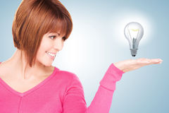 Woman showing light bulb on the palm of her hand Stock Images
