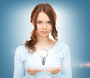 Woman showing light bulb on the palm of her hands Royalty Free Stock Image