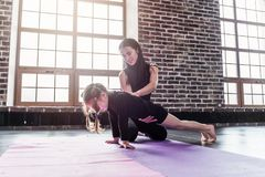 Woman showing little girl how to do plank exercise in fitness studio.  stock image