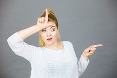 Woman showing loser gesture with L on forehead. Woman showing mean sign, lame or loser gesture with L fingers on forehead, grey background Royalty Free Stock Images