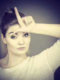Woman showing loser gesture with L on forehead Royalty Free Stock Photo
