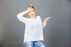 Woman showing loser gesture with L on forehead Royalty Free Stock Photography