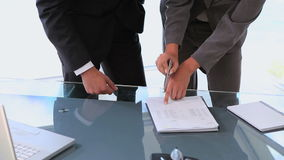 Woman showing man where to sign in a contract. On the table stock video footage