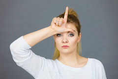 Woman showing loser gesture with L on forehead Stock Images