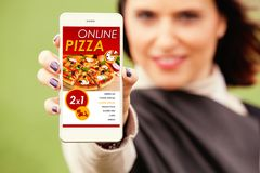 Woman showing mobile phone with Pizza shop app in the screen. Royalty Free Stock Photo