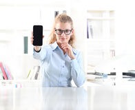 Woman showing mobile phone sitting at desk in office Stock Photos