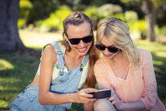 Woman showing mobile phone to her friend Stock Images