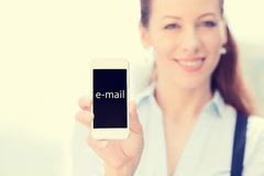 Woman showing mobile smart phone with e-mail sign on screen. Smiling female hold mobile smart phone with e-mail sign on screen isolated outside city background stock images