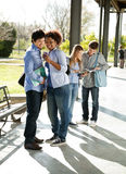Woman Showing Mobilephone To Classmate At. Full length of happy young women showing mobilephone to classmate while friends standing in background at university Stock Photos
