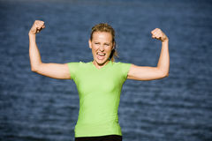 Woman showing muscles. A woman showing her muscles with a smile on her face Royalty Free Stock Photos