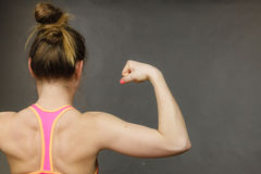 Woman showing muscles of the back and shoulders. Woman athletic young girl showing muscles of the back and shoulders on black background. Beauty fit female body Royalty Free Stock Photos