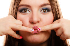 Woman showing nails heart design. Love valentines day concept. Funny girl covers her mouth with hand showing pink emotional heart nails design on white stock photography