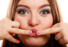 Woman showing nails heart design. Love valentines day concept. Funny girl covers her mouth with hand showing pink emotional heart nails design on white royalty free stock photography