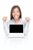Woman showing netbook laptop. Excited woman sitting pointing at netbook laptop screen with copy space. Asian / Caucasian woman sitting at table isolated on white Stock Images
