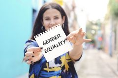 Woman showing a notepad with the text gender equality. Closeup of a young woman outdoors showing a notepad with the text gender equality written in it royalty free stock image