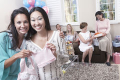 Woman Showing Off Gift At Baby Shower. Portrait of a happy women with friend showing off gift at baby shower royalty free stock images