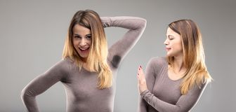 Woman disgusted by body odor. Woman showing off her body while her sister is disgusted by her sweety armpit - pit stains concept Royalty Free Stock Photo