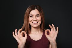 Woman showing OK gesture in sign language on black. Background royalty free stock photography