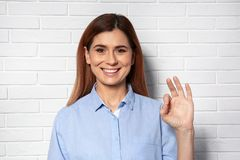 Woman showing OK gesture in sign language near wall. Woman showing OK gesture in sign language near brick wall royalty free stock photo