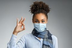 Woman showing okay gesture. Photo of healthy african american woman wears protective mask against infectious diseases and flu. Health care concept royalty free stock images